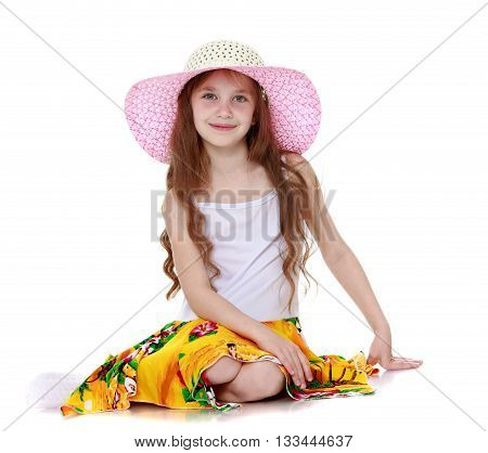 Adorable little long-haired girl in a light summer dress and a large pink Panama sits on the floor-Isolated on white background