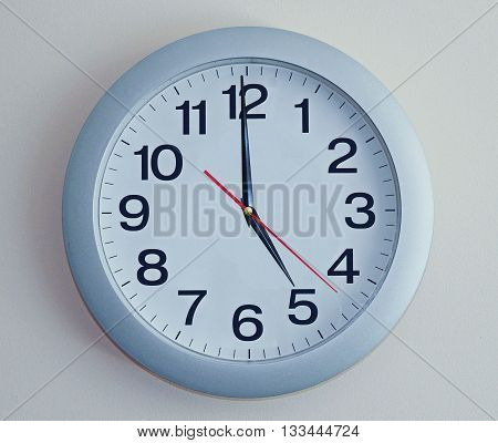 Wall Clock.  Light blue clock with arrows.
