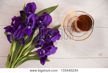 Cup of black tea and blue iris flowers on a light background