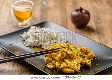 curry chicken and oriental rice in a blak dish