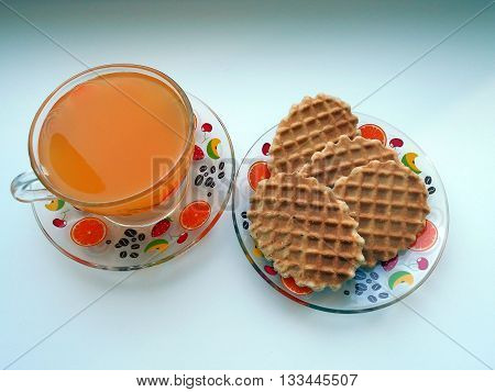 In a cup fruit juice is poured. On a saucer cookies lie