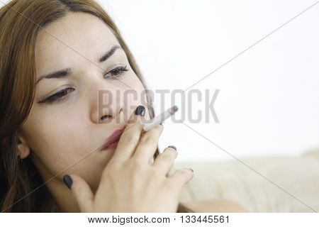 Woman holding a cigarette between the fingers and smoking at home