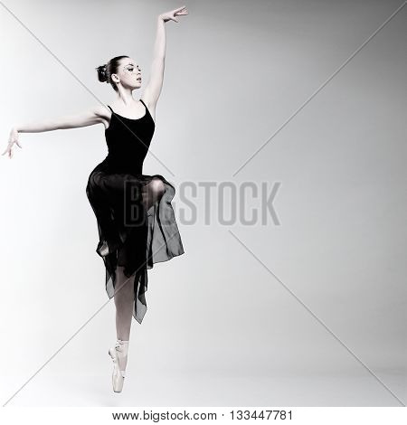 Beautiful ballet-dancer, modern style dancer posing on studio background