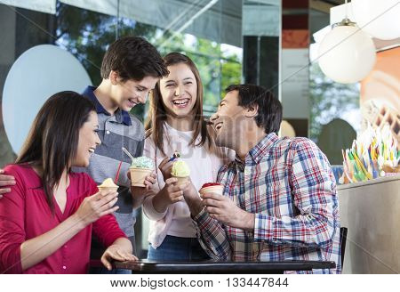 Family Laughing While Having Ice Creams In Parlor