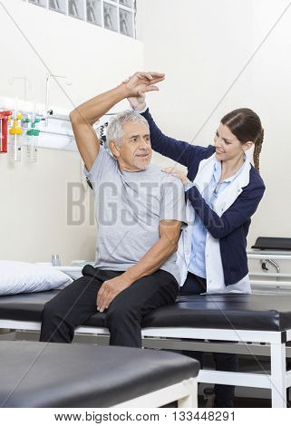 Physiotherapist Assisting Senior Patient To Exercise