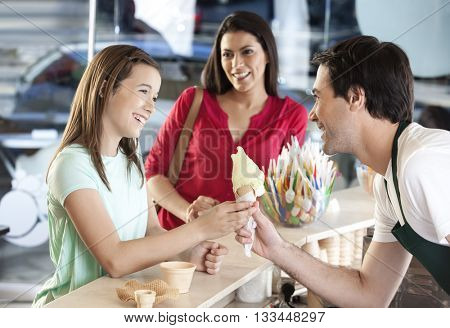 Girl Receiving Ice Cream Cone From Waiter By Mother