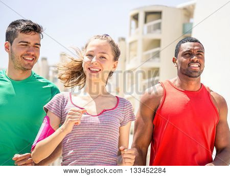 Young runners training day closeup on urban background - Multiracial friends jogging in city under summer sun - Concept of friendship and fitness together -