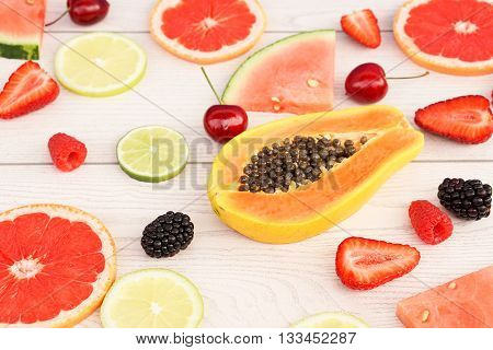 Mixed fruit on wood side view - Berries and lemon with papaya at the center of the composition