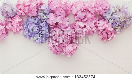 Fresh hydrangea flowers. Natural hydrangea flowers in a border on a rustic background. Top view, vintage toned image, blank space