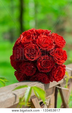 wedding bouquet of red roses lying on a wooden fence