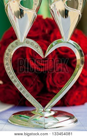glasses in the form of heart on the background of the wedding bouquet of red roses