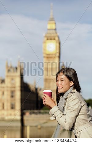 London city business woman drinking morning coffee looking over Westminster bridge near Big Ben, UK. Urban Asian businesswoman or female tourist happy in fall/spring, filtered image with golden sun.