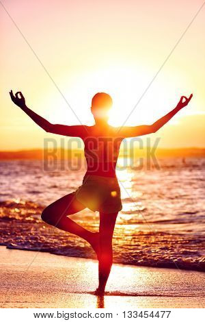 Wellness of mind - Yoga woman standing on one leg doing tree pose with open raised arms in sunset flare in front of the ocean on beach. Mindfulness and meditation concept.