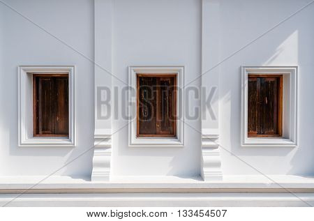 Architecture of Thailand's public temple's wall with three wooden windows with evening sunlight and shadow