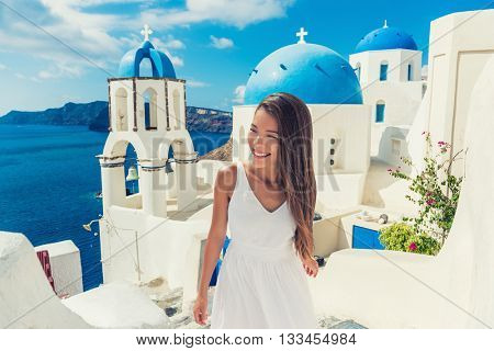 Santorini travel tourist woman on vacation in European destination walking on stairs. Asian girl in white dress visiting three blue domes in Oia village, greek island. Summer Europe holidays.