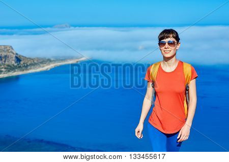 female traveler with backpack standing on the cliff against sea and blue sky at early morning. Balos beach on background, Crete, Greece