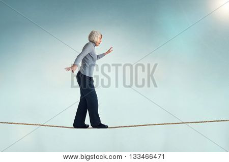 senior caucasian woman walking on a tightrope