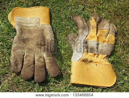 Pair of dirty gardening gloves on a lawn