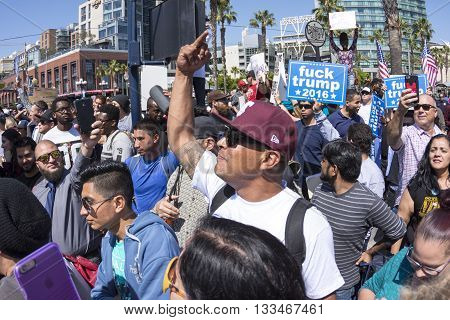 SAN DIEGO USA - MAY 27 2016: Among a huge anti-Trump crowd a protester displays the vulgar middle finger at a group of Trump supporters outside a Trump rally at the San Diego Convention Center.