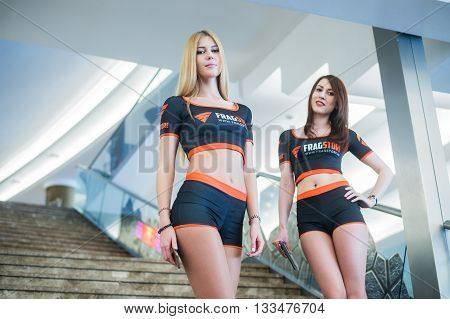 MOSCOW, RUSSIA - MAY 13 2016: EPICENTER MOSCOW Dota 2 cybersport event. Beautiful promo girls over ladder on the background