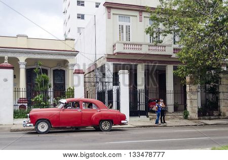 HAVANA - DECEMBER 10: American classic car goes down the street on 10 December 2015 in Havana, Cuba. Brightly colored vintage American cars are very popular in Havana.