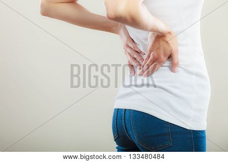 Long working hours and health. Young female with backache. Woman with back pain on gray