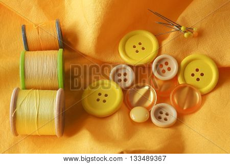 A collection of haberdashery items with a yellow theme - buttons dressmaker's pins and cotton on bobbins. All on a piece of yellow fabric.