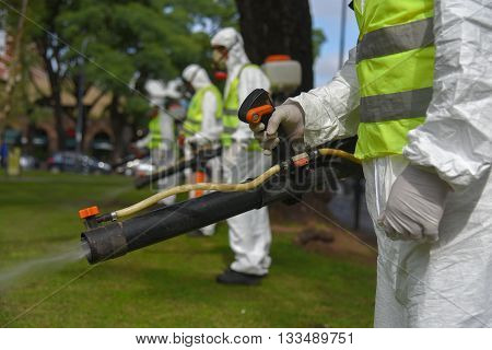 Buenos Aires Argentina - March 3 2016: Employees of the Ministry of Environment and Public Space fumigates for Aedes aegypti mosquitos to prevent the spread of Zika virus and dengue fever in park.