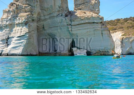 MELOS GREECE - SEPTEMBER 4 2012: A boat and kayakers exploring Kleftiko. The caves and rock formations were used by pirates for hideouts.