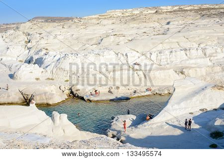 MELOS GREECE - SEPTEMBER 4 2012: Sarakiniko cove with people sunbathing and swimming.