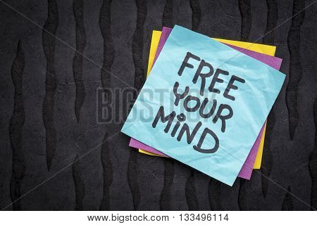 free your mind reminder note - handwriting on a sticky note against black Nepalese lokta paper