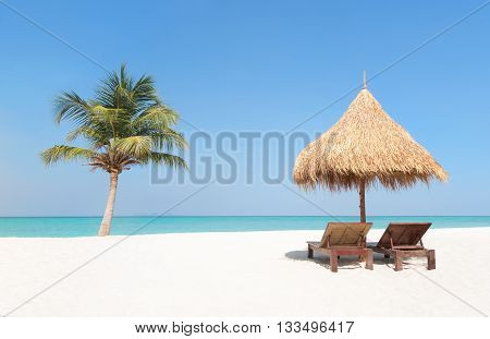 Wooden Deckchairs, Straw Parasol And Palm Tree On Paradise Beach.