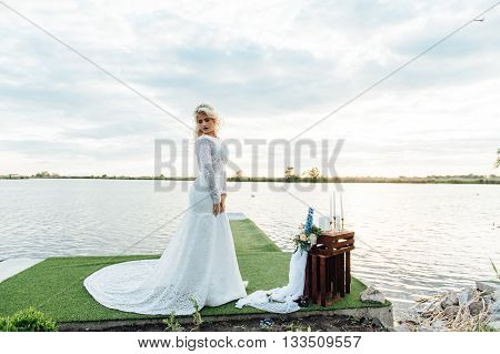 Beautiful young bride woman in luxury wedding dress with red lips makeup and long wavy hairstyle. Beauty girl portrait posing near water outdoor photo.