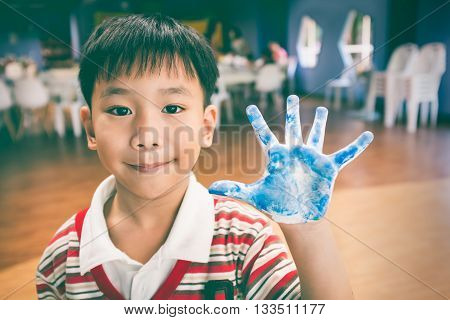 Cute asian painter shows his painted palm on art class. Positive human emotion. Strengthen the imagination of child for education and learning concept. Vintage tone.
