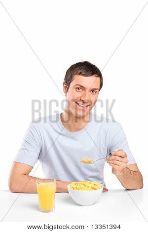 Smiling Young Man Eating Cornflakes At Breakfast