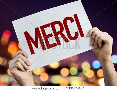 Thank You (in French) placard with night lights on background