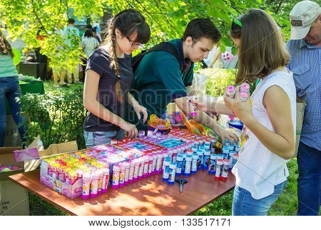 Zaporizhia/Ukraine- June 5, 2016: volunteers unpacking and preparing presents - soap bubbles for children on charity family festival organized in regions with most quantity of refugees from Donetsk area, occasioned with International Children`s Day