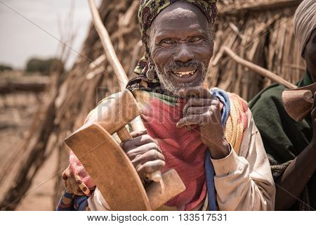 OMORATE ETHIOPIA - 16 AUGUST 2015: unidentified old man from Arbore tribe carry in his hands a traditional wooden chair used also as a neckrest