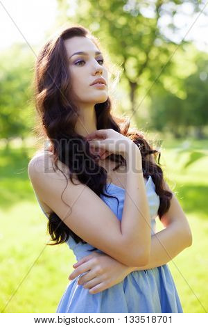 Portrait of a beautiful young Caucasian woman in a spring garden. Sweet girl, clean skin, long dark hair.