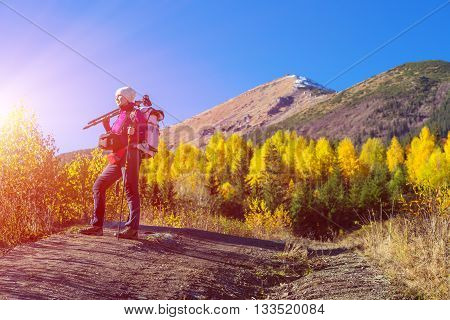 Autumnal Forest and Mountains and Woman Hiker Portrait with Sun Shining and Blue Sky