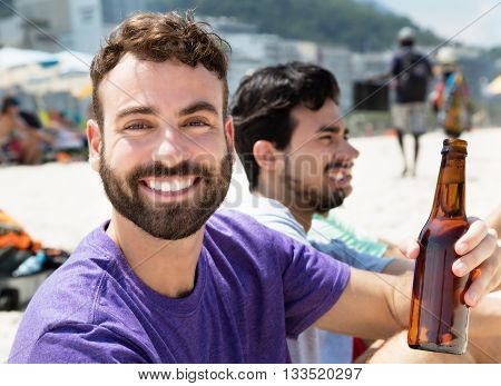 Caucasian drinking beer with friends outside at beach in the summer