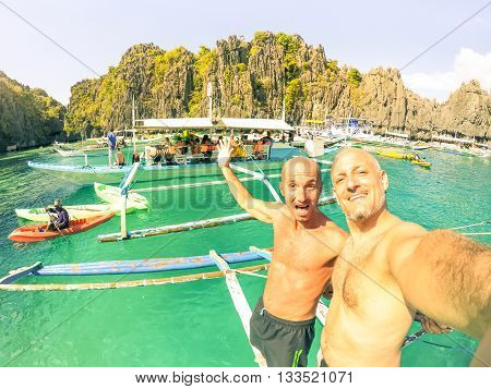 Friends tourists having fun taking selfie at Big Lagoon in El Nido Palawan - Cheerful guys on boat at paradisiacal Philippines islands - Concept of joyful moment in tropical travel vacation