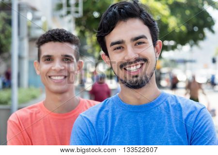 Laughing mexican guy with friend outside in the city in the summer