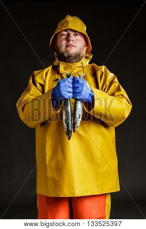Man dressed as a commercial fisherman wearing traditional protective oilskins Sou'Wester hat and holding mackerel fish.