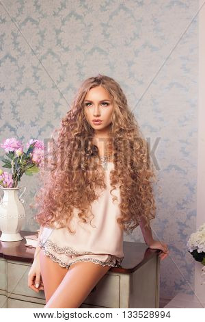 Sexy blonde woman with fashion make-up and curly hair. Skin and hair care concept
