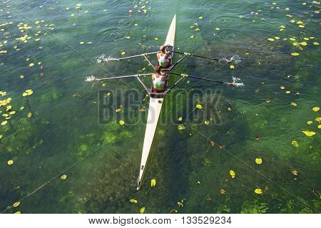 Two rowers in a boat rowing on the tranquil lake