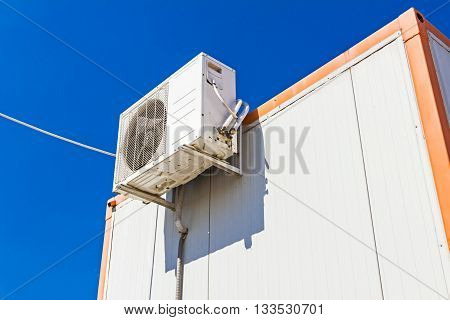 Outdoor unit compressor of air conditioner is placed on white container office.