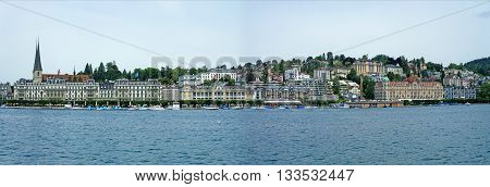 View from the Lake Lucerne on Lucerne, Switzerland; promenade with many houses, hotels and a church, photo of the lake, panoramic