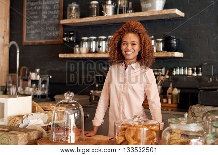 Portrait of an attractive young woman standing behing the counter of a cafe