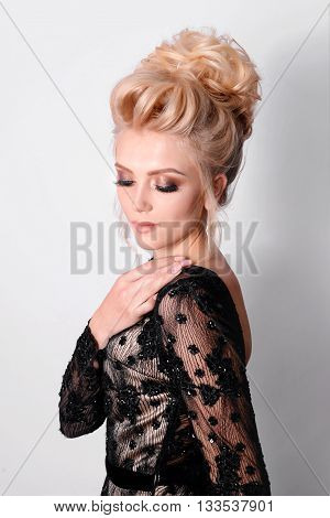 Beautiful lady in elegant black evening dress with updo hairstyle. Fashion photo